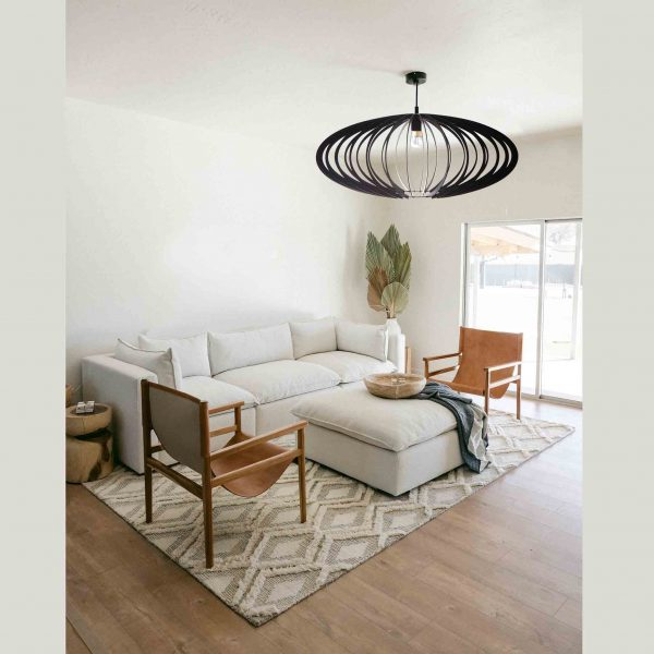 The Pinot pendant light in black hanging over a small living room with neutral decor