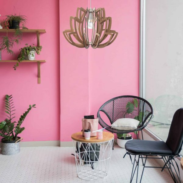 The Lotus wooden pendant light hanging in a trendy cafe