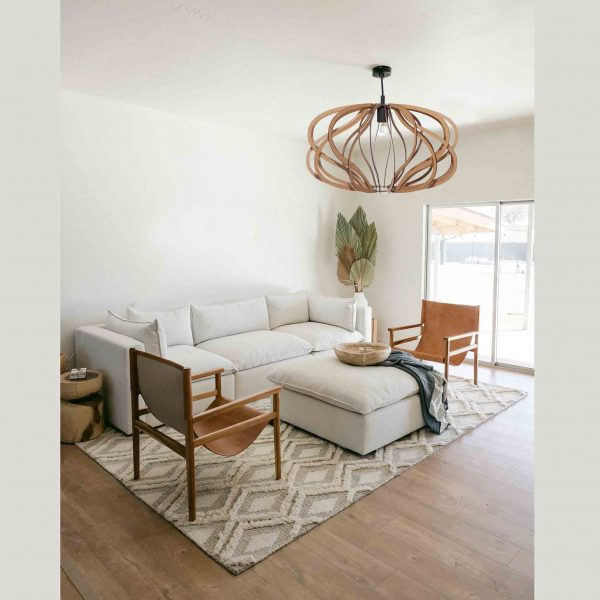The Virgo pendant light in natural with a black cordset in a sitting room with neutral decor