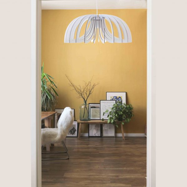 The Scorpio pendant light in white against a yellow feature wall
